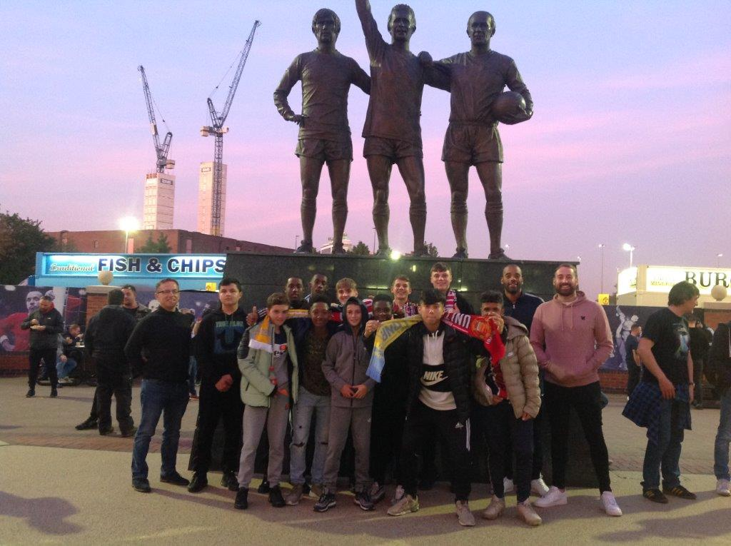 John Willmott pupils in front of the statue of George Best, Dennis Law and Bobby Carlton at Old Trafford.
