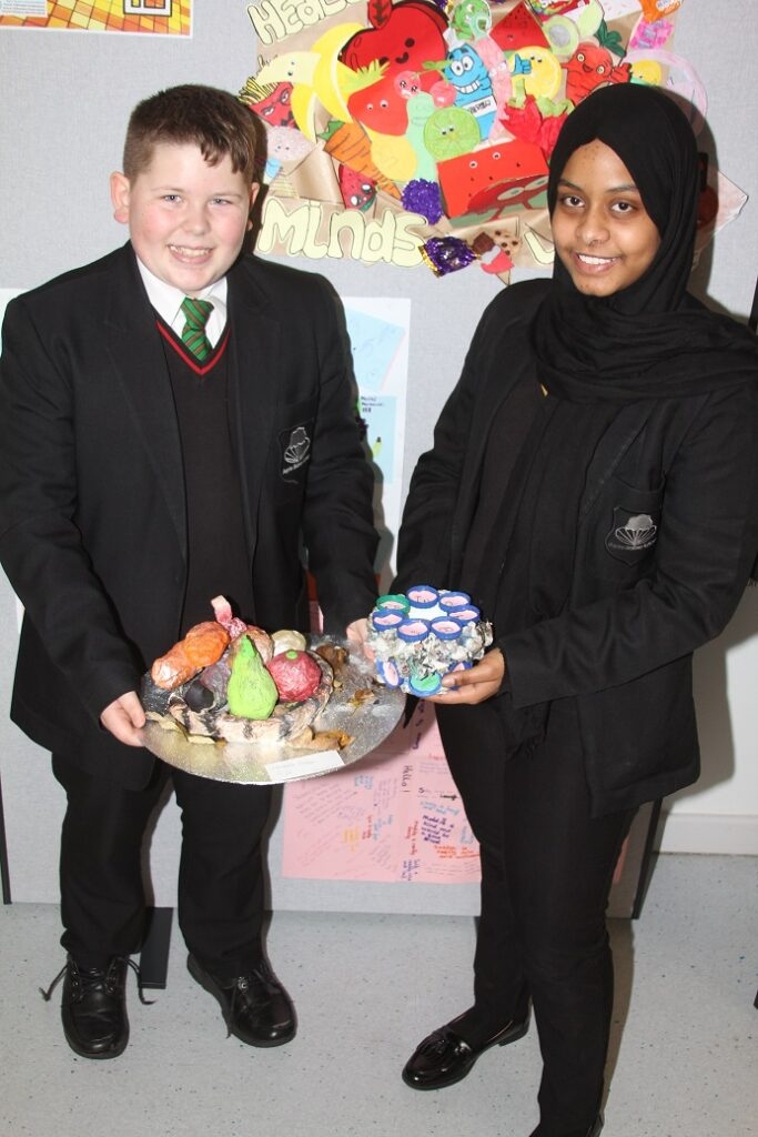 Alexandru Harbea, 12, and Weam Ahmed, 14, with art they created from recycled material.