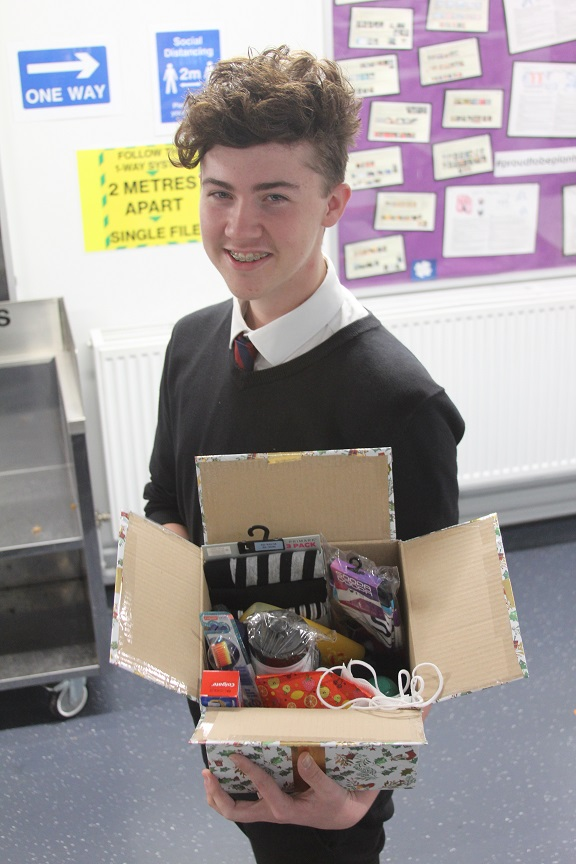 Big-hearted Plantsbrook student Ben Songhurst with one of the Christmas care parcels he is creating.