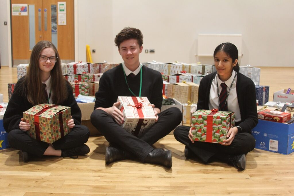 Ben Songhurst with Ellie Holmes and Amrita Dhutti and some of the care parcels created by the Plantsbrook Sixth Former's appeal.