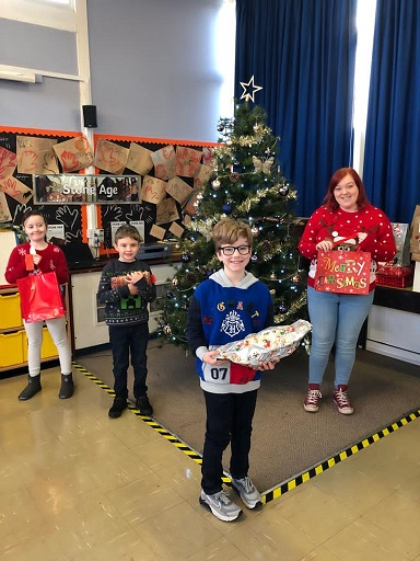 Teacher Kim Brown with Year 3-4 children and just some of the gifts they have collected for residents at Orchard Blythe Nursing Home in Coleshill.
